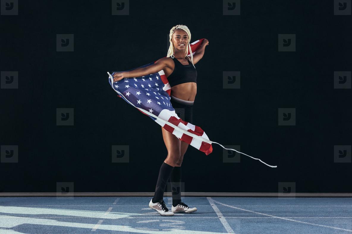 Female athlete walking on running track holding american flag