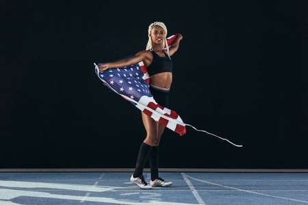 Female athlete walking on running track holding american flag