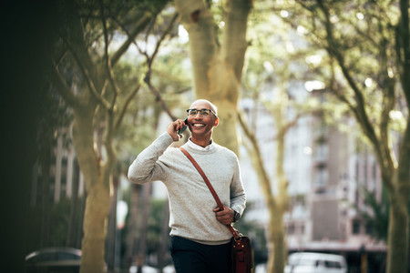 Businessman talking over mobile phone while commuting to office