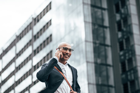 Businessman talking over mobile phone walking outdoors