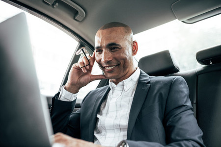 Businessman looking at laptop sitting in car