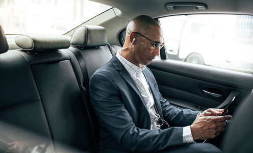 Businessman sitting in car using mobile phone