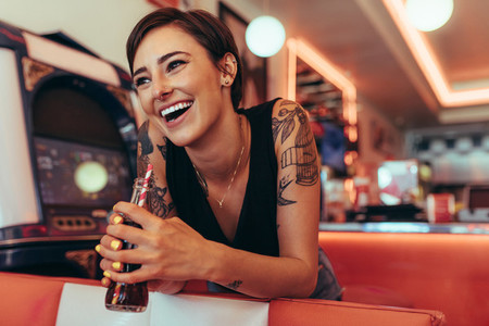 Woman at a restaurant holding a soft drink
