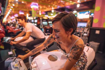 Woman riding an arcade racing bike