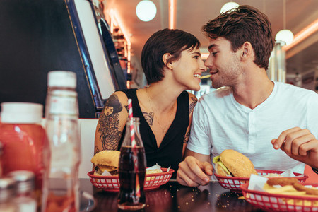 Coupe in romantic mood sharing a french fry at a restaurant