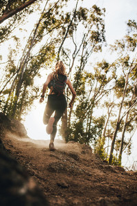 Woman running up hill on mountain trail