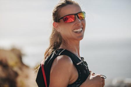 Female mountain runner smiling at camera