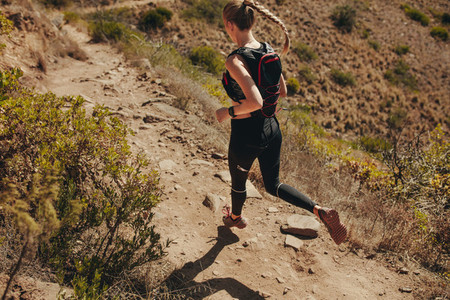 Woman running on rocky trails in mountains