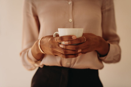 Woman in formal attire holding a coffee cup