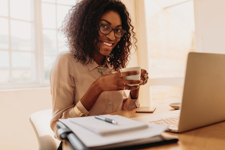 Businesswoman enjoying a cup of coffee while working on laptop a