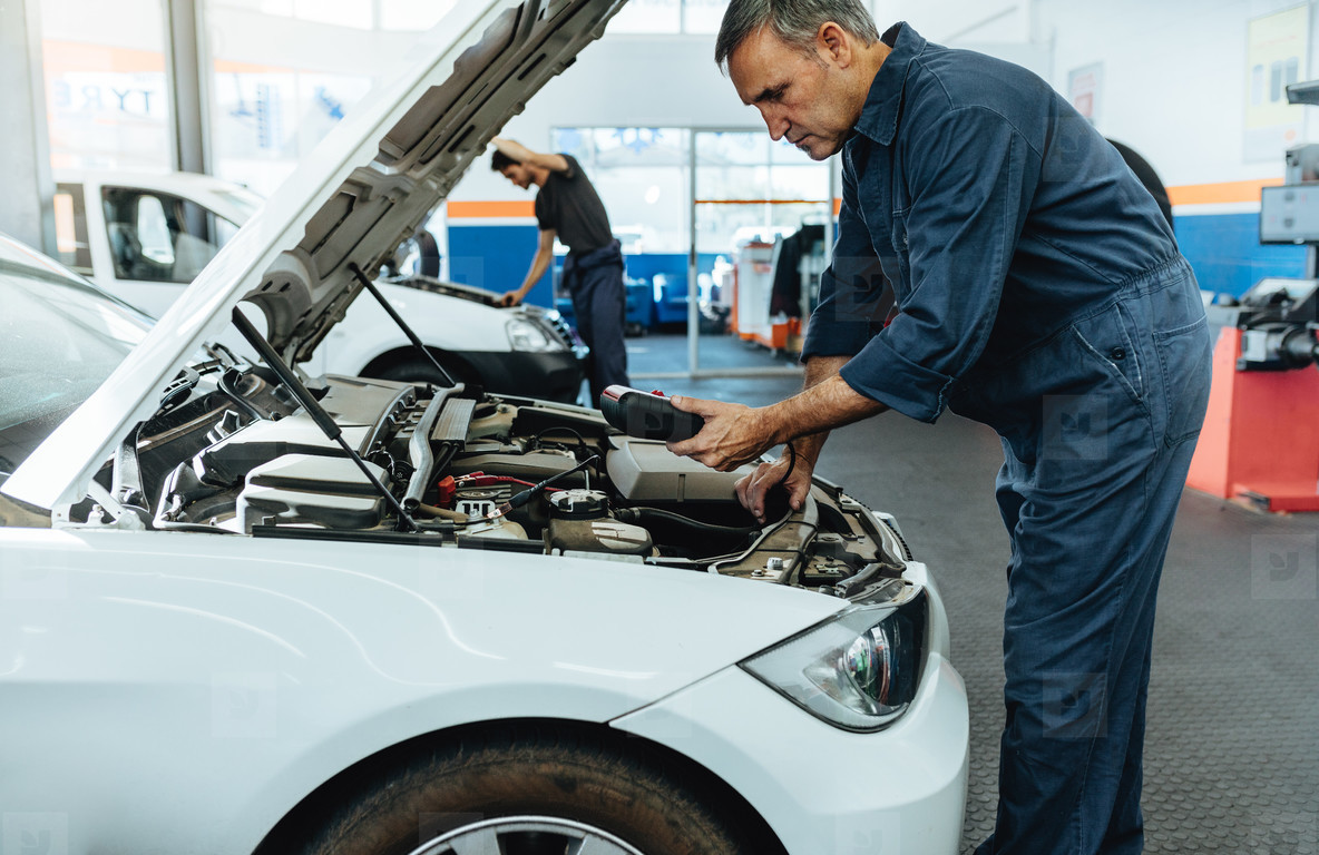 Mechanic reading the error codes with diagnostic device