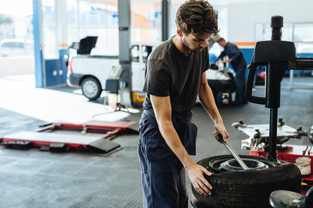 Mechanic changing car tire in service station
