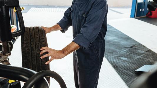 Mechanic doing car tire checkup on machine