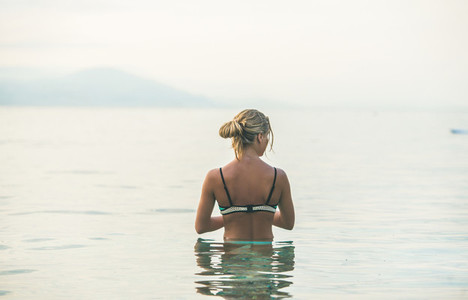 Young woman standing in still sea waters in Alanya Turkey