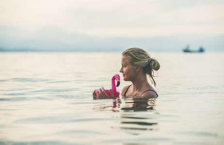 Young woman swimming with flamingo toy Alanya Turkey