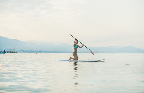 Young beautiful slavian woman tourist practicing paddle boarding