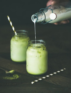 Refreshing iced coconut matcha latte and hand pouring milk