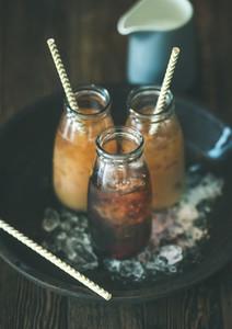 Cold Thai iced tea in bottles with milk dark background