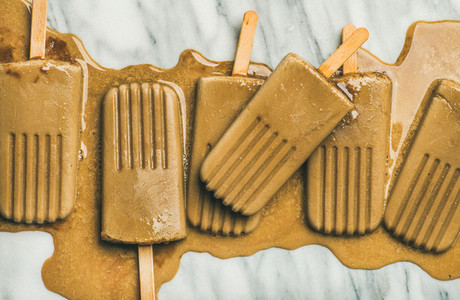 Flatlay of melting coffee latte popsicles on grey background