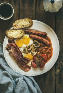 English breakfast with fried eggs  sausages  mushrooms  bacon  beans  coffee