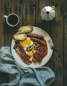 Traditional English breakfast with fried eggs  sausages  mushrooms  bacon