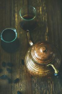Oriental tea pot black tea in tulip glasses and raisins
