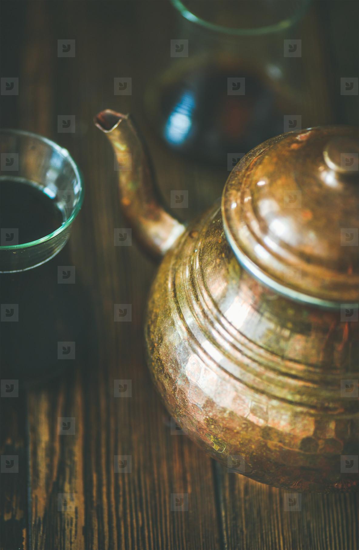 Oriental tea pot and black tea in tulip glasses