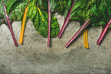 Flat lay of fresh leaves of swiss chard over concrete background