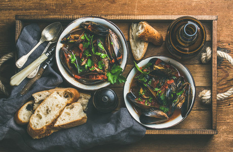 Flat lay of Belgian boiled mussels in tomato sauce with parsley