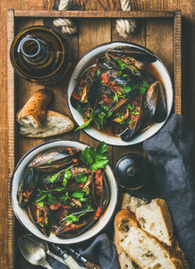 Flat lay of boiled mussels in tomato sauce and light beer
