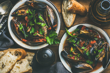 Boiled mussels in tomato sauce and beer over wooden background