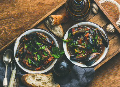 Belgian boiled mussels in tomato sauce with parsley  copy space