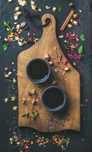 Chinese black tea in black stoneware cups on wooden board