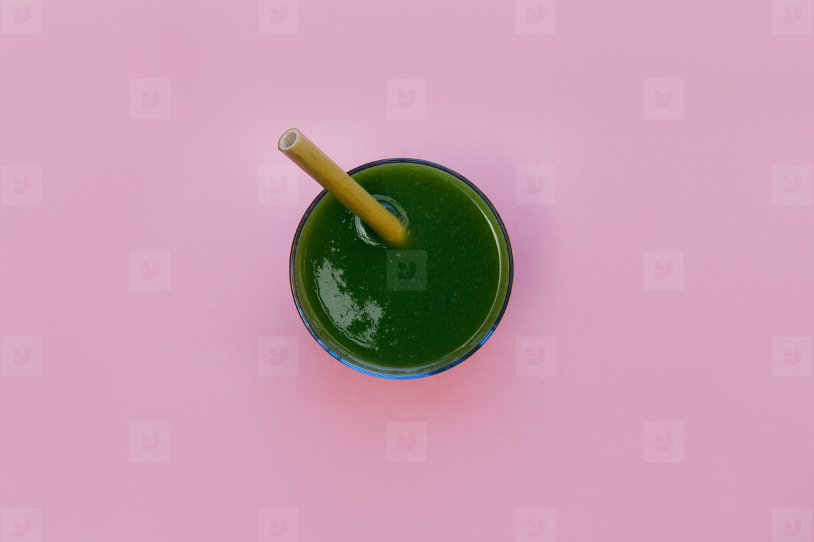 Green smoothie drink isolated on pink background