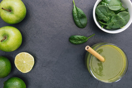 Green smoothie drink with straw on dark background copy space