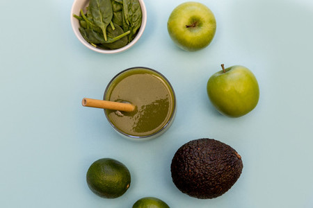 Green smoothie drink blue background top view