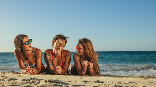 Woman friends relaxing at the beach and talking