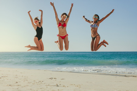 Women jumping in air at the beach