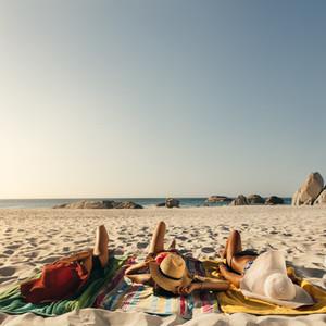 Women relaxing at the beach wearing sun hats