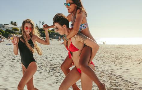 Woman friends sunbathing and enjoying on beach