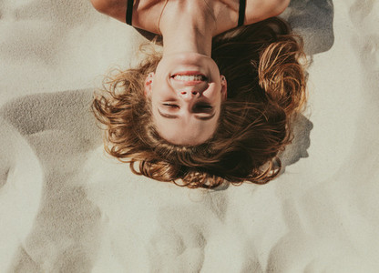 Close up of woman relaxing on beach sand