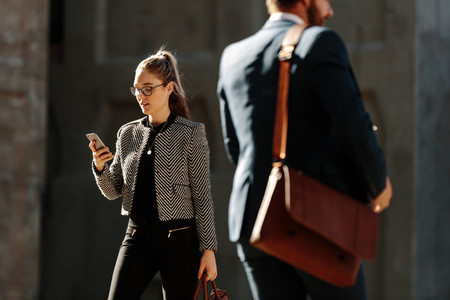 Businesswoman using mobile phone while going to office