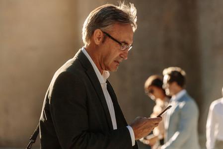 Senior man using mobile phone while walking on street to office