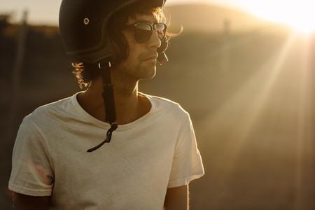Biker in helmet and sunglasses standing outdoors
