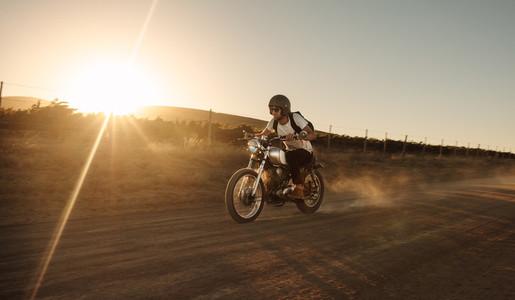 Biker driving a vintage motorcycle on dirt road