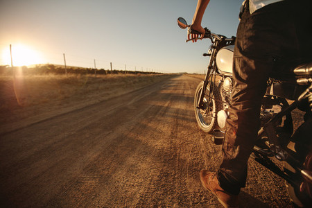 Rider standing on rural road with his bike