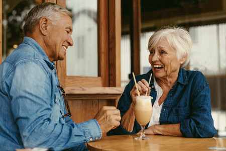 Cheerful senior couple sitting at table in cafe