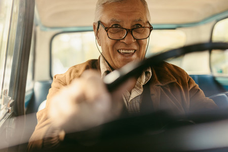 Happy old man enjoying driving his car