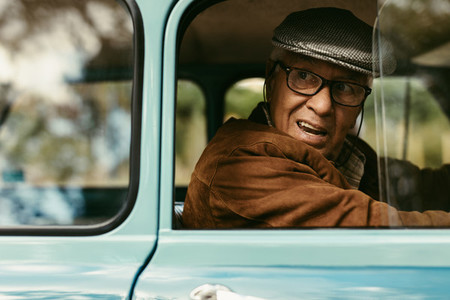Elderly man driving a vintage car