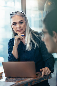 Mature business woman paying attention in meeting